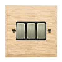 Picture of 3 Gang 10AX 2 Way Rocker / Antique Brass / Woods Light Oak Chamfered Edge with Black Surround Inserts