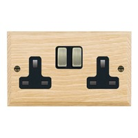Picture of 2 Gang 13A Double Pole Switched Socket / Antique Brass / Woods Light Oak Chamfered Edge with Black Surround Inserts